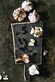 Stilleben mit frischem Knoblauch und fermentierten schwarzen Knoblauchzehen