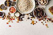 Variety of dried fruits, nuts, honey and oat flakes in ceramic bowls for cooking healthy breakfast muesli or granola energy bars