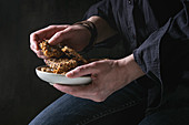 Woman holding ceramic plate with homemade energy oats granola bars with dried fruits and nuts