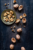 Walnuts and nutshells over black wooden background