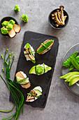 Springlike vegan nigiri sushi with smoked tofu, mushrooms and vegetables on white marble board
