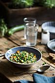 Gemüsesuppe mit Erbsen, Karotten, Zucchini und Kichererbsen auf Holztisch