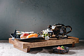Sushi Set nigiri and sushi rolls on japanese wooden serving board with soy sauce, chopsticks, ceramic tea pot