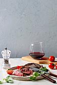 Gegrilltes Beefsteak serviert mit Feldsalat, Kirschtomaten und Rotwein