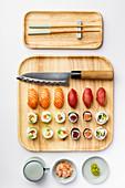 Verschiedene Sushi auf Holzplatte daneben Stäbchen, Ingwer und Wasabi (Japan)