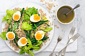 Bean, barley and egg salad with forks and a bowl of dressing