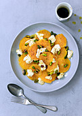 Savoury orange and bocconcini salad with a jug of spicy dressing