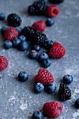 Raspberries, blackberries and blueberries with water droplets, photographed on a blue surface