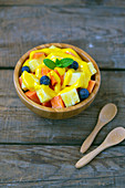 Juicy pieces of papaya with blueberries garnish by yellow sauce and mint leaf in bowl beside wooden spoons