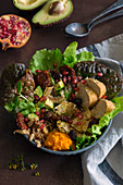 Bowl of delicious lettuce and avocado salad with pieces of bread and pomegranate seeds