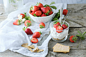 Creamy sweet dessert with fresh juicy tasty strawberries served inside a glass on a rustic wooden table