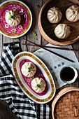Composition of ceramic plates with Chinese meal baozi with checkered towel on wooden table