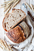 Homemade fresh sourdough bread in tablecloth on wooden table