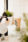 Tasty milk bubble tea with tapioca pearls in plastic cup on table in traditional Taiwanese cafe