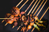 Cooked hot mushroom skewer over table with delicious grilled skewers with meat, fish, squid and broccoli
