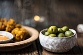 Green olives in a bowl, with chicken crispies and a dip