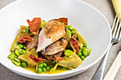 Chicken breast on peas and artichokes