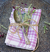 A fabric napkin with a silver spoon and a sprig of thyme