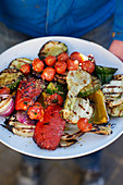Man holding a big tray of mixed grilled vegetables