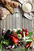 an arrangement of fresh vegetables, bread and bread dough
