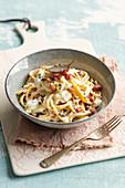 Spaghettoni alla carbonara mit Stracciatella, frittiertem Salbei und Pistazien