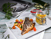 Crispy fried bream filet with tomatoes, vegetables, and couscous