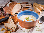 Parsnip cream soup with garlic chips, cress and rye bread