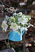 Sträußchen aus Blüten von Christrosen und Schneeglöckchen an Stuhllehne gehängt