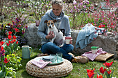Frau mit Hund Zula genießt den Frühlingsgarten