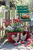 Frühlingsflirt im roten Holzkübel: Goldlack 'Winter Passion', Poem 'Lavender' und Schleifenblume 'Candy Ice', Holzhühner, Osternest mit roten Ostereiern