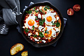 Shakshuka with tomatoes, peppers, onions and eggs prepared in cast iron skillet