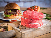 Raw hamburger patties, hamburgers, vegetables and spices