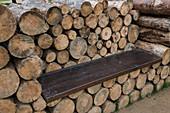Brennholzstapel mit Sitzbrett