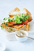Sandwich with fried chicken on chiabatta with tomatoes, cheddar cheese, cucumber, onion, salad and microgreens