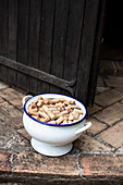 Wine corks in n enamel bowl in front of a wooden door