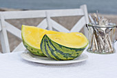 A yellow watermelon and cutlery on a table