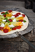 Unbaked pizza with tomatoes, zucchini flowers, mozzarella and basil