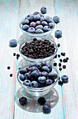 Blueberries (fresh, dried and frozen) in glass bowls