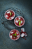 Gin and Tonic with pomegranate seeds in glasses with sugared rims, ice and limes
