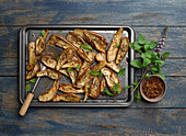 Roasted eggplant on baking sheet with spices and basil