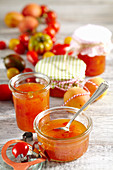 Homemade apricot and tomato jam in preserving jars