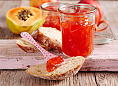 Papaya and nectarine jam in a mason jar on a wooden background