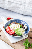 Almond and sesame seed granola with strawberries and avocado on a wooden board on a bed