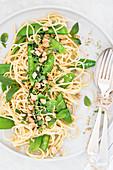 Spaghetti with mange tout, basil and peanuts