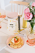 Waffles and fruit on table festively set with candle and vase of peonies