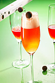 Moulin Rouge cocktails made with apricot brandy, gin, lemon juice, grenadine and champagne with chocolate pralines
