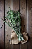 From above of bundle of green asparagus on wooden table