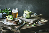 Toasts with green cashew pate and slices of cucumber on wooden board