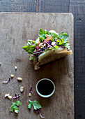 From above of delicious traditional Gua Bao sandwich with parsley and grain sprouts served on board with sauce