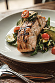 Woodfire-grilled salmon with Swiss chard and tahini salad, tomato and cucumber